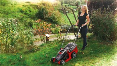 Junge Frau mit Rasenmäher
